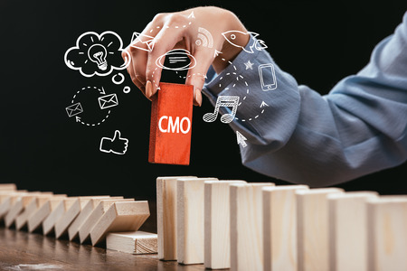 cropped view of woman picking red block with word cmo out of wooden bricks, icons on foreground