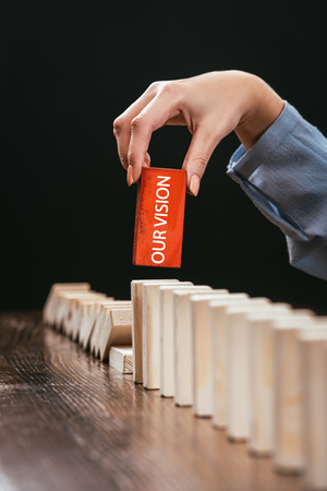 partial view of woman picking red wooden brick with word 'our vision' from row of blocks on desk isolated on black Banque d'images