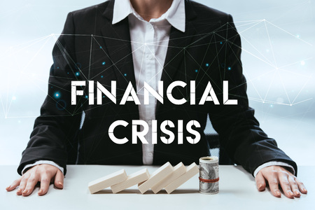 cropped view of businesswoman with wooden blocks and money roll on table and 'financial crisis' lettering on foreground 写真素材 - 116464714