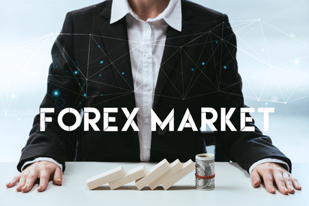 cropped view of businesswoman with wooden blocks and money roll on table and forex market lettering on foreground Banco de Imagens