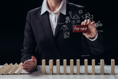 cropped view of businesswoman holding red brick with for rent words while preventing wooden blocks from falling, icons on foreground