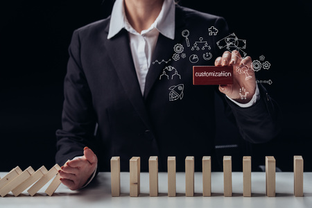 cropped view of businesswoman holding red brick with 'customization' word while preventing wooden blocks from falling, icons on foreground Stockfoto