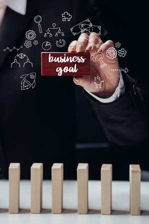 cropped view of woman holding red wooden brick with words business goal isolated on black, icons on foreground