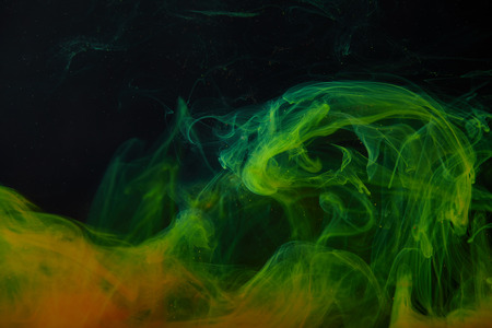 dark background with abstract green and orange swirls of paint Banco de Imagens