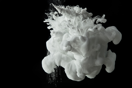 white splash of paint flowing in water on black background