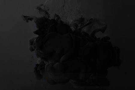 Black paint splash on dark background