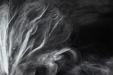 Abstract flowing swirls of grey paint on black background Banco de Imagens