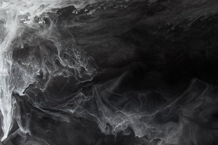 Abstract flowing swirls of grey paint on black background Imagens