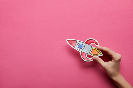 top view of hand holding rocket on pink background Stock Photo