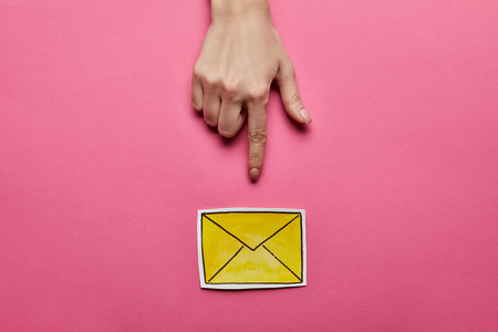 top view of hand pointing at yellow mail sign on pink background