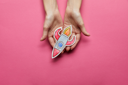 top view of hands holding rocket on pink background