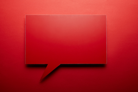 empty speech bubble in red color on red background Фото со стока