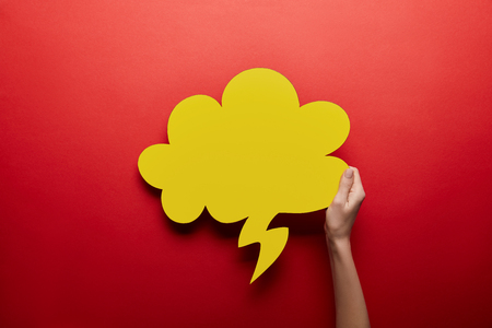 top view of empty yellow thought bubble on red background