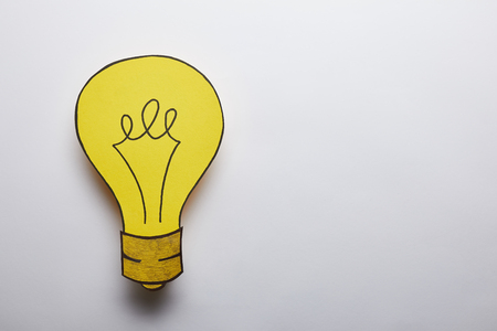 top view of yellow light bulb idea symbol on grey background