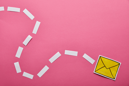 top view of yellow sending delivering email sign on pink background