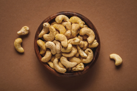 Top view of cashew nuts in wooden bowl on brown background Reklamní fotografie
