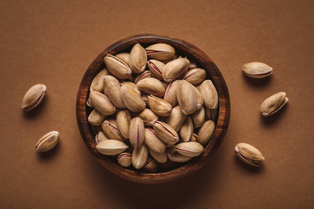Top view of pistachio nuts in wooden bowl on brown backdrop