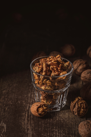 Close up view of shelled walnuts in glass on wooden surface Stock Photo