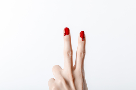 cropped view of woman showing peace sign with dripping red nail polish isolated on grey