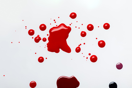 top view of abstract red spills with drops isolated on grey
