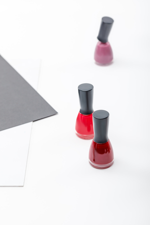 top view of three bottles of red, burgundy and pink nail polish on white