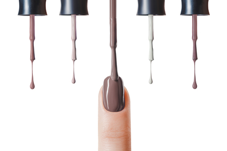 brown nail polish on fingernail with wet brush isolated on white