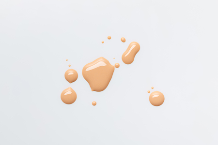 top view of wet and shiny caramel drops of nail polish isolated on grey Stockfoto
