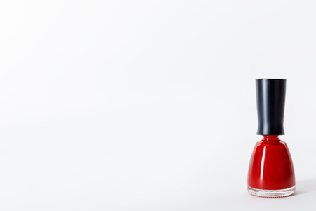 Bottle of bright red nail polish on white Фото со стока