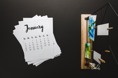 Top view of January calendar and paintings on clothespins on black Archivio Fotografico - 116388569