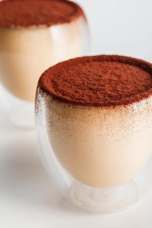 close up of tiramisu desserts with cocoa powder