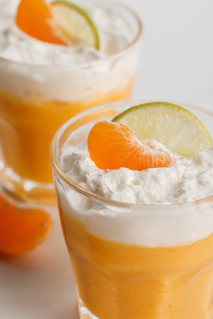 close up of glasses with orange mousse with tangerine and lime slices