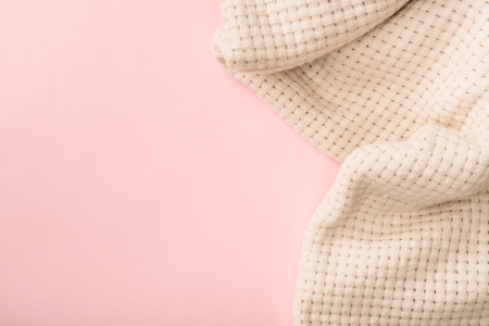 top view of white knitted blanket on pink background