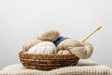 close up view of yarn with knitting needles in wicker basket on grey backdrop