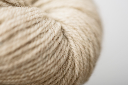 full frame of beige knitting clew on grey background