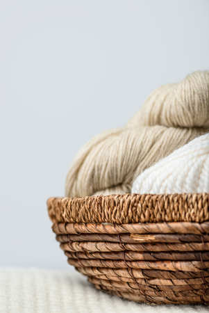 close up view of yarn clews in wicker basket on grey backdrop