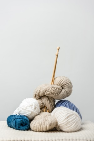 close up view of knitting clews with knitting needles on grey backdrop