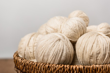 close up view of yarn balls in wicker basket on grey background