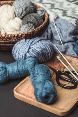 close up view of knitting, scissors and knitting needles on dark tabletop with blanket Stock fotó