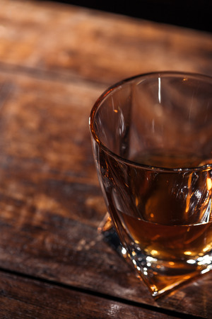 close-up view of glass of luxury whiskey on wooden table