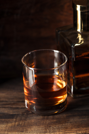 close-up view of glass of bourbon and bottle on wooden table