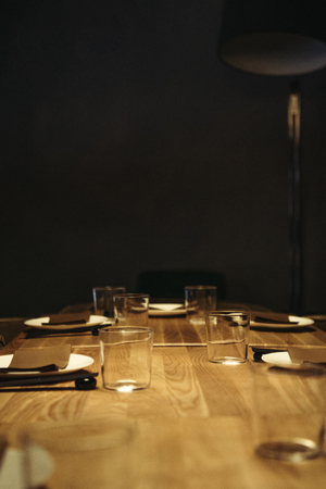 selective focus of table setting on wooden surface with black background and copy space Stock Photo
