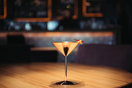 delicious alcoholic cocktail in metal glass decorated with chili pepper and nacho chip on dark background