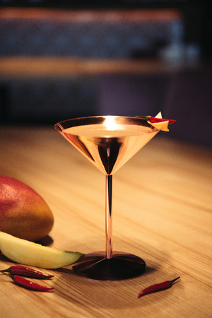 selective focus of alcoholic cocktail in metal glass decorated with chili pepper, nacho chip and mango on wooden table Stock Photo