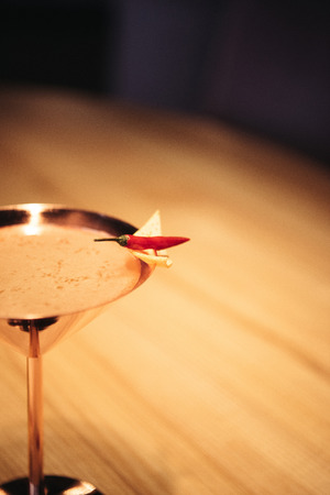 selective focus of alcoholic cocktail in metal glass decorated with chili pepper and nacho chip on wooden table
