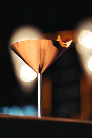 selective focus of alcoholic cocktail in metal glass decorated with chili pepper and nacho chip on dark background Stock Photo