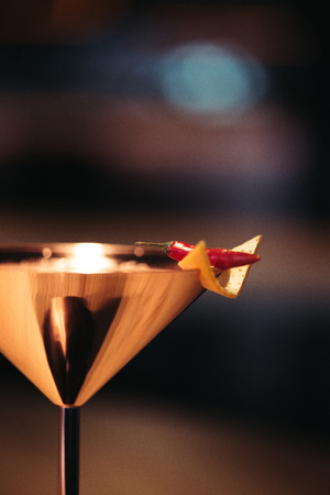 close up of alcoholic cocktail in metal glass decorated with chili pepper and nacho chip on dark background Stock Photo