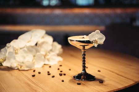 selective focus of alcoholic cocktail in metal glass decorated with orchid flower and coffee beans on dark background Stock Photo
