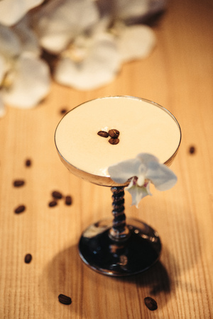 alcoholic cocktail in metal glass decorated with orchid flower and coffee beans on wooden table