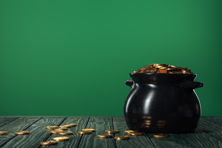 Golden coins in pot isolated on green with copy space, st patrick day concept