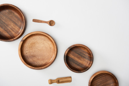 top view of wooden bowls, spoon and spatula on white background